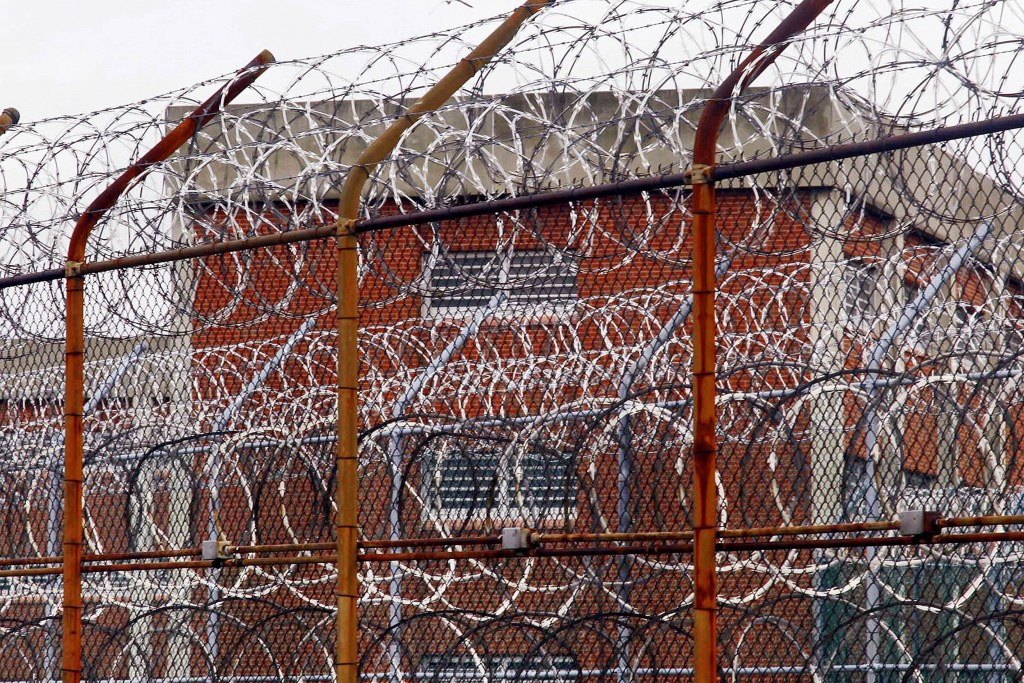 FILE - In this March 16, 2011, file photo, a security fence surrounds inmate housing on the Rikers Island correctional facility in New York. Health ex...