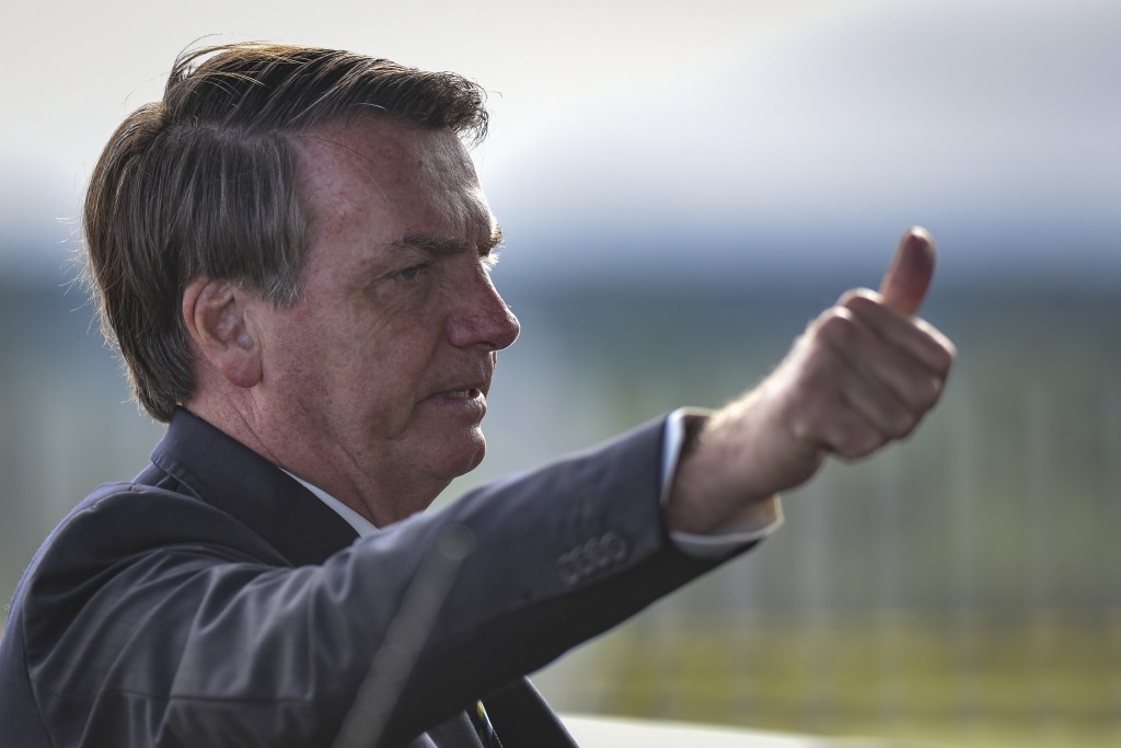 Brazil's President Jair Bolsonaro greets supporters and journalists as he arrives to give a news conference on the new coronavirus at Planalto preside...