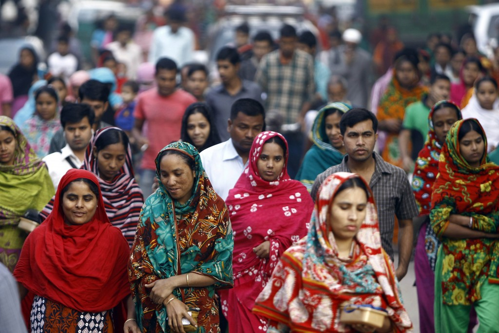 FILE - In this Feb. 13, 2014 file photo, Bangladeshi garment workers arrive for work early morning in Dhaka, Bangladesh. A survey of factory owners in...