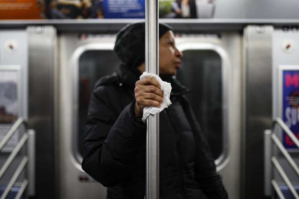 A subway customer uses a tissue to protect her hand while holding onto a pole as COVID-19 concerns drive down commuters, March 19, 2020, in New York. ...