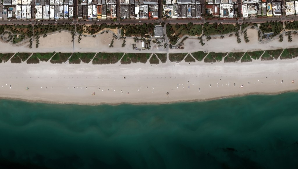 This Friday, March 27, 2020, satellite image provided by Maxar Technologies shows an empty area in Miami Beach, Fla. amid an outbreak of the new coron...