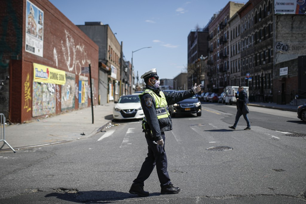 An NYPD traffic officer wearing personal protective equipment directs vehicles at a barricade after the city closed down a section of Bushwick Avenue ...