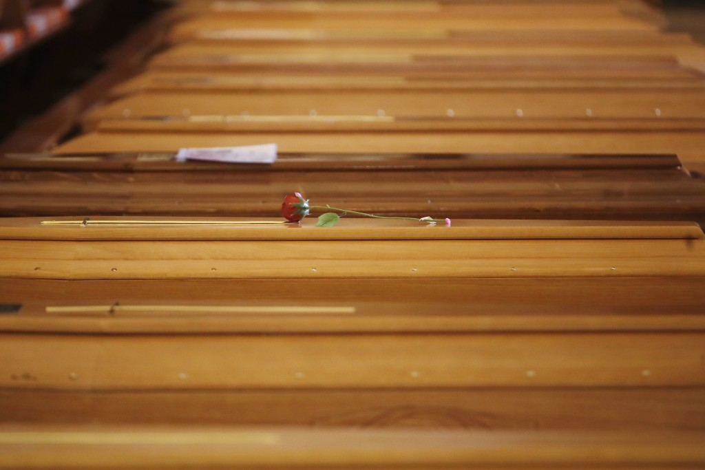 A red rose lies on a coffin lined up along others inside the San Giuseppe church in Seriate, Italy, to be blessed before being sent to crematoriums in...