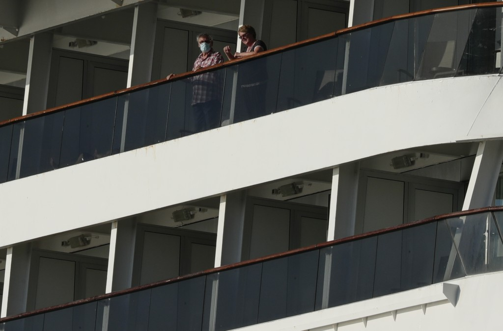 Passengers, one wearing a protective face mask, look out from the Zaandam cruise ship, anchored in the bay of Panama City, Friday, March 27, 2020. Sev...