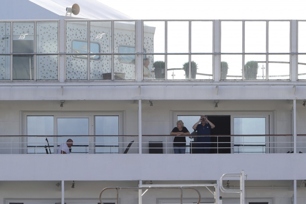 In this Friday, March 27, 2020, photo, passengers are seen on the cruise ship Artania docked at Fremantle harbour in Fremantle, Australia. Authorities...