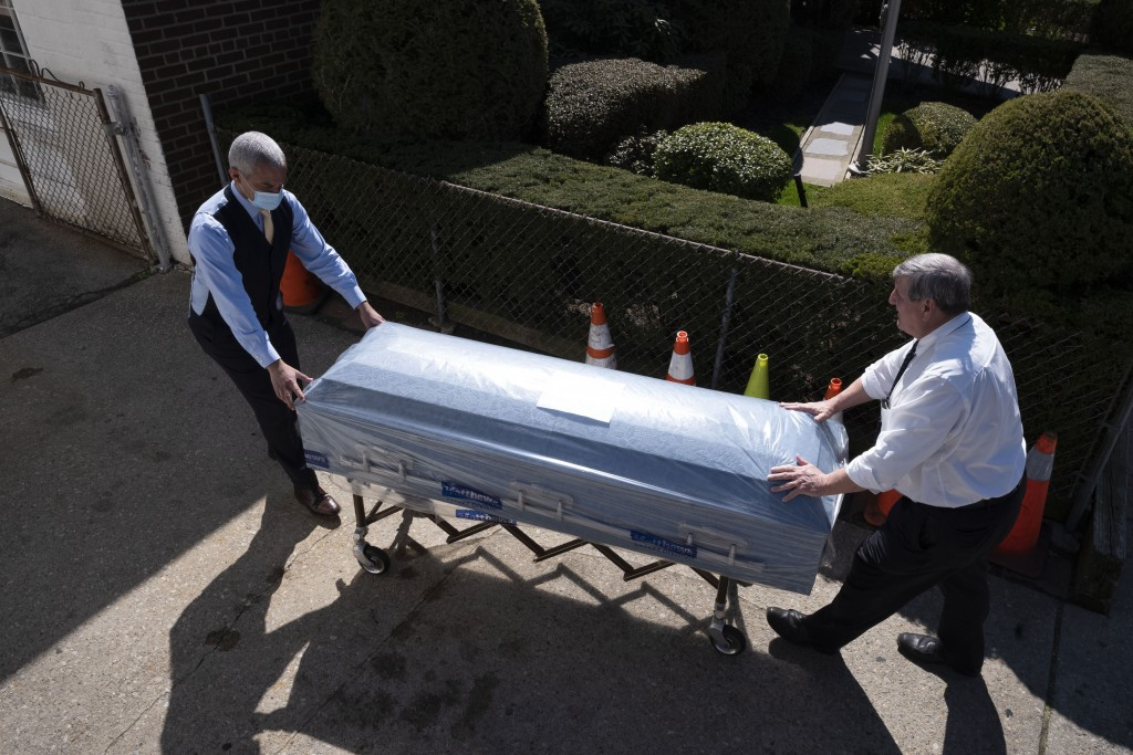 Omar Rodriguez, left, works with Joe Neufeld, the owner of the Gerard Neufeld Funeral Home, to move a newly delivered casket into the Queens business,...