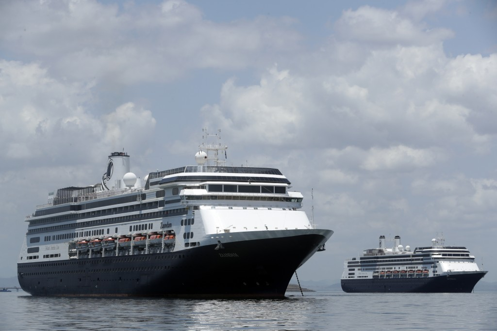 The Zaandam cruise ship, left, carrying some guests with flu-like symptoms, is anchored shortly after it arrived to the bay of Panama City, Friday, Ma...