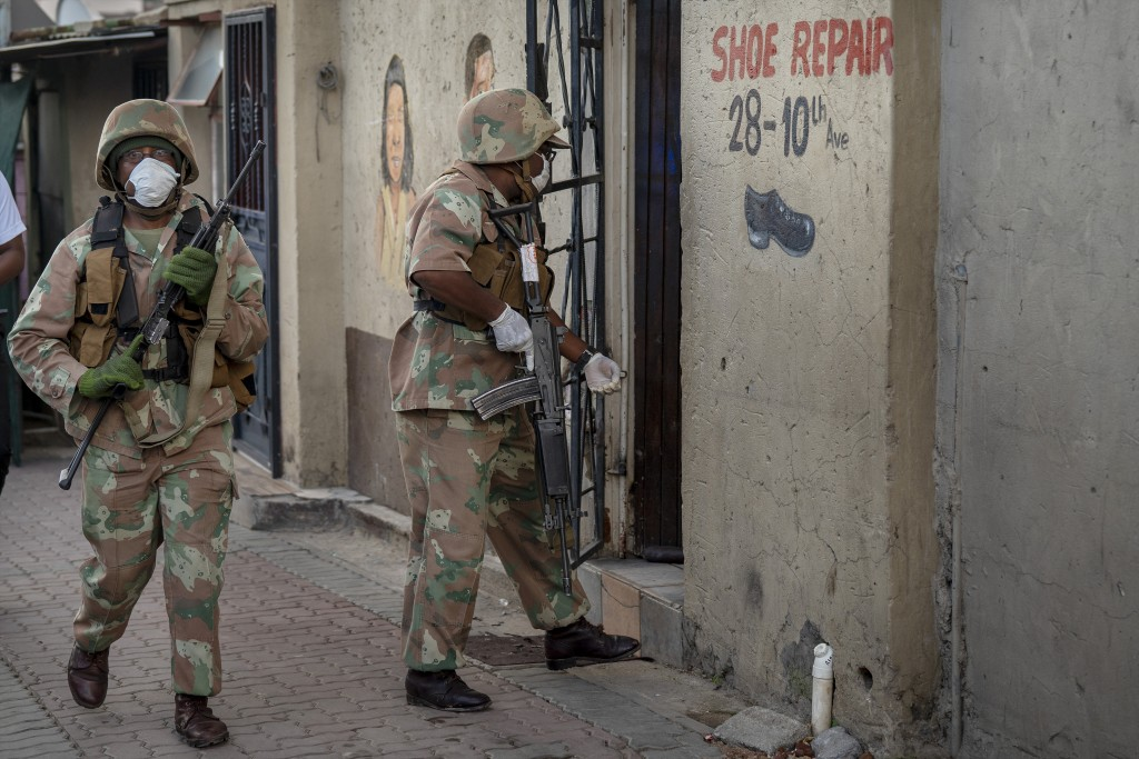 South African National Defense Forces patrol the densely populated Alexandra township east of Johannesburg Friday, March 27, 2020. South Africa went i...