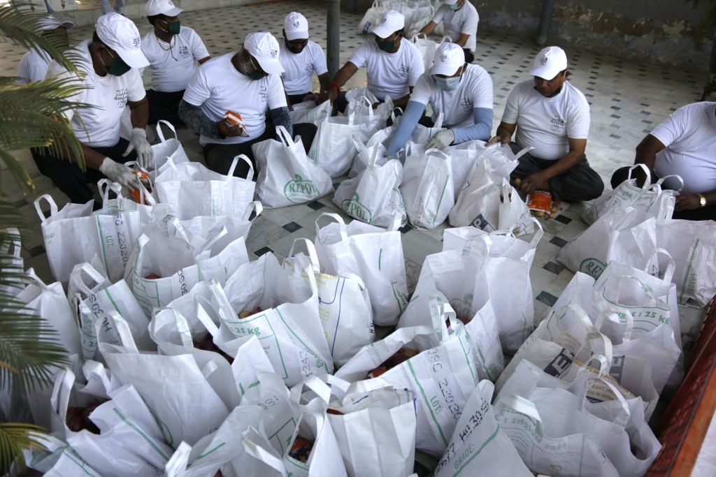 Indian volunteers makes essential item's kit to distribute to the needy people in Ahmedabad, India, Sunday, March 29, 2020. Indian Prime Minister Nare...