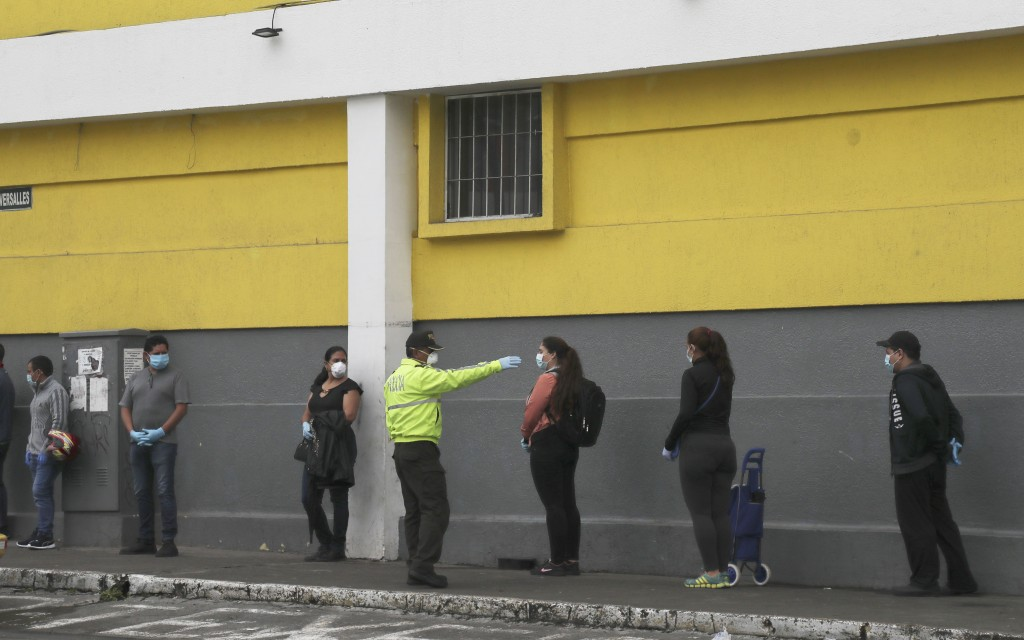 A police officer instructs shoppers to maintain a social distance as a precaution against the spread of the new coronavirus, as they wait in line to e...