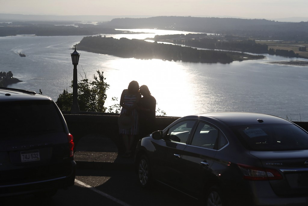 In this July 22, 2019, photograph, a couple look over the Columbia River as the suns sets from the Vista House at Crown Point State Park near Corbett,...