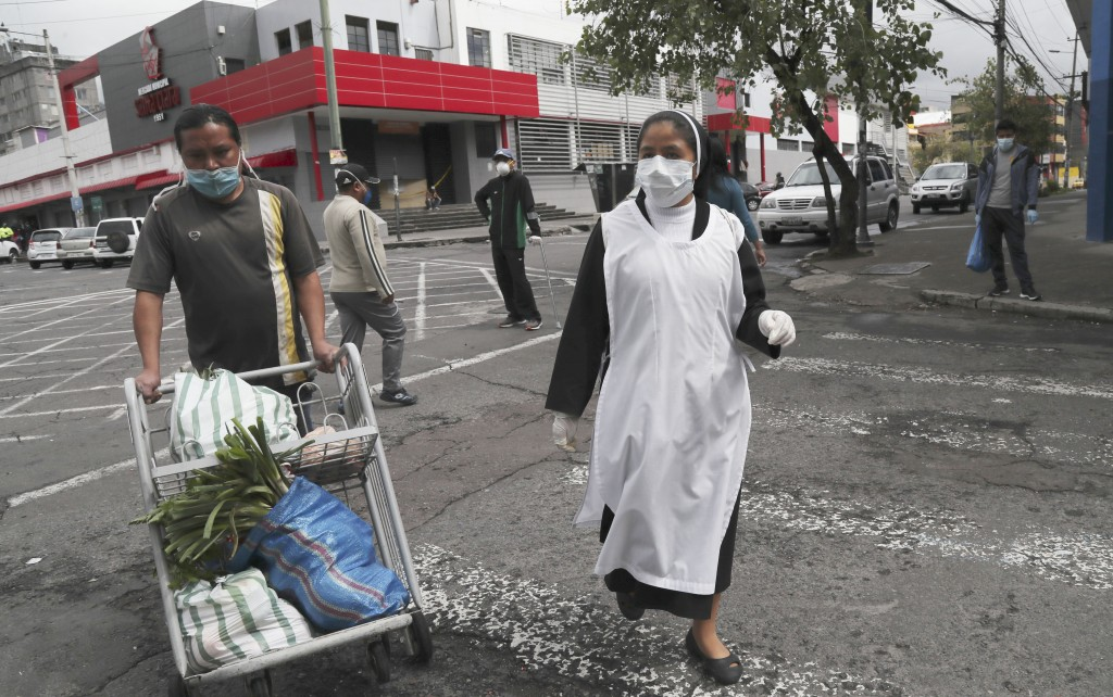 A nun, wearing a protective face mask and disposable gloves as a precaution against the spread of the new coronavirus, and a worker carting her grocer...