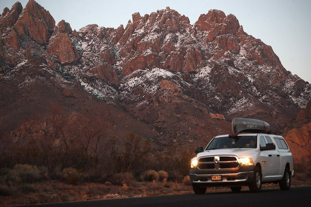 In this Thursday, March 4, 2020, photograph, a motorist carries a canoe on the roof his pickup truck while leaving the Organ Mountains Desert Peaks Na...