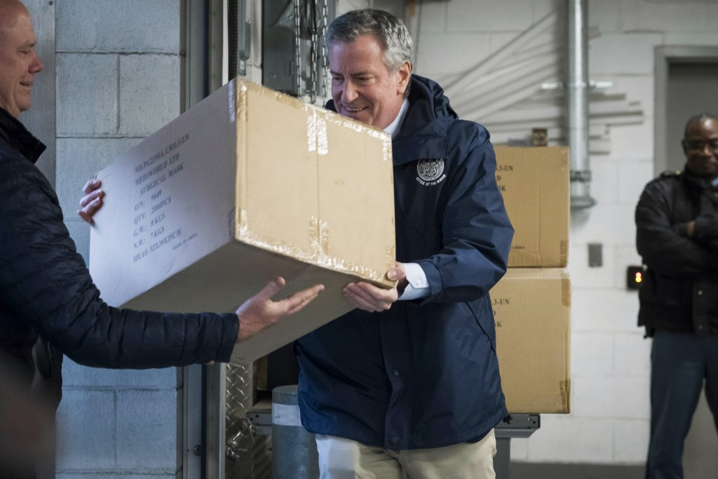 In this March 28, 2020 photo provided by the New York City Mayoral Photography Office, NYC Mayor Bill de Blasio helps load a carton containing some of...