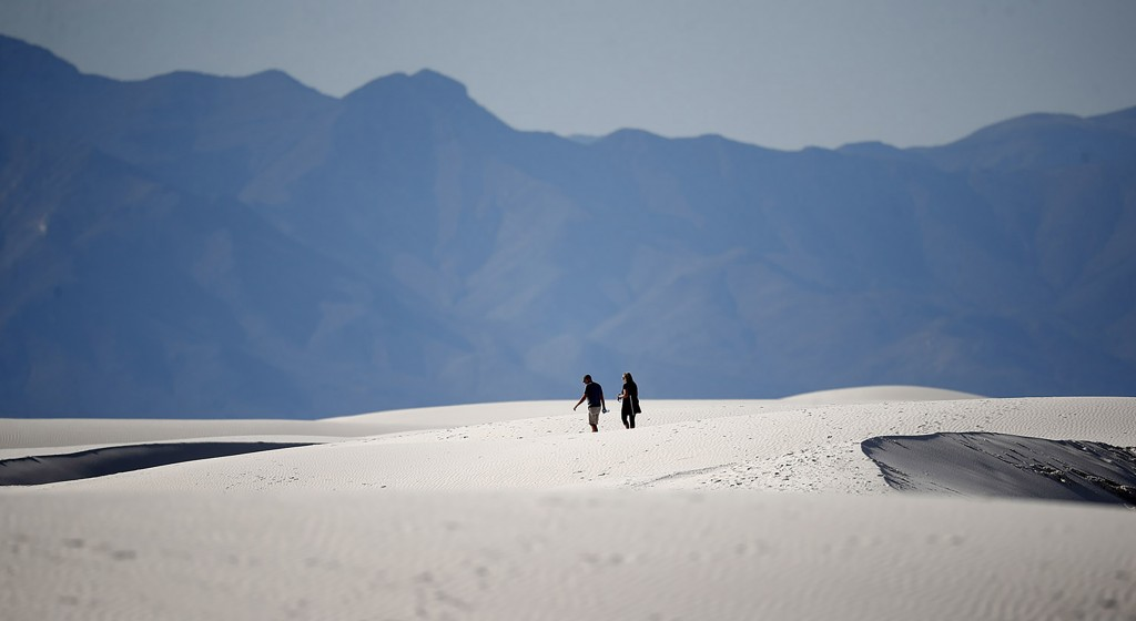 In this Thursday, March 5, 2020, photograph, a couple walks over gypsum dunes in White Sands National Park at Holloman Air Force Base, N.M. With the n...