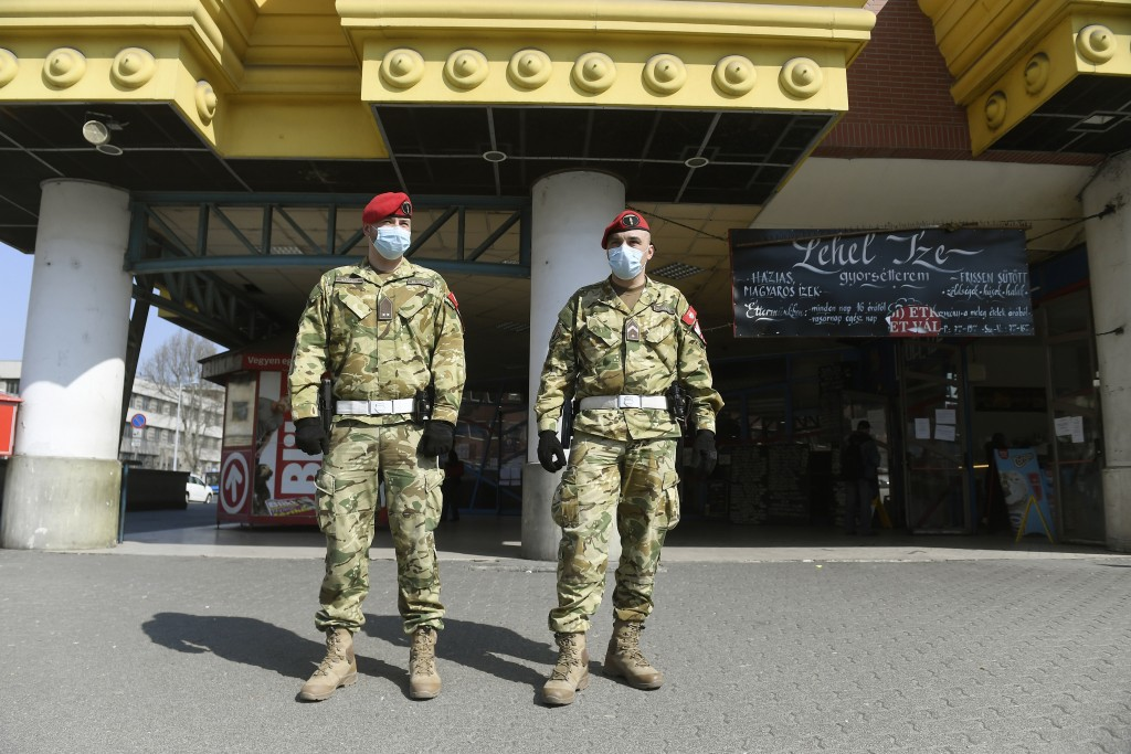 Military policemen patrol the Lehel square market in Budapest, Hungary, Sunday, March 29, 2020. Due to the coronavirus outbreak from 28 March a curfew...