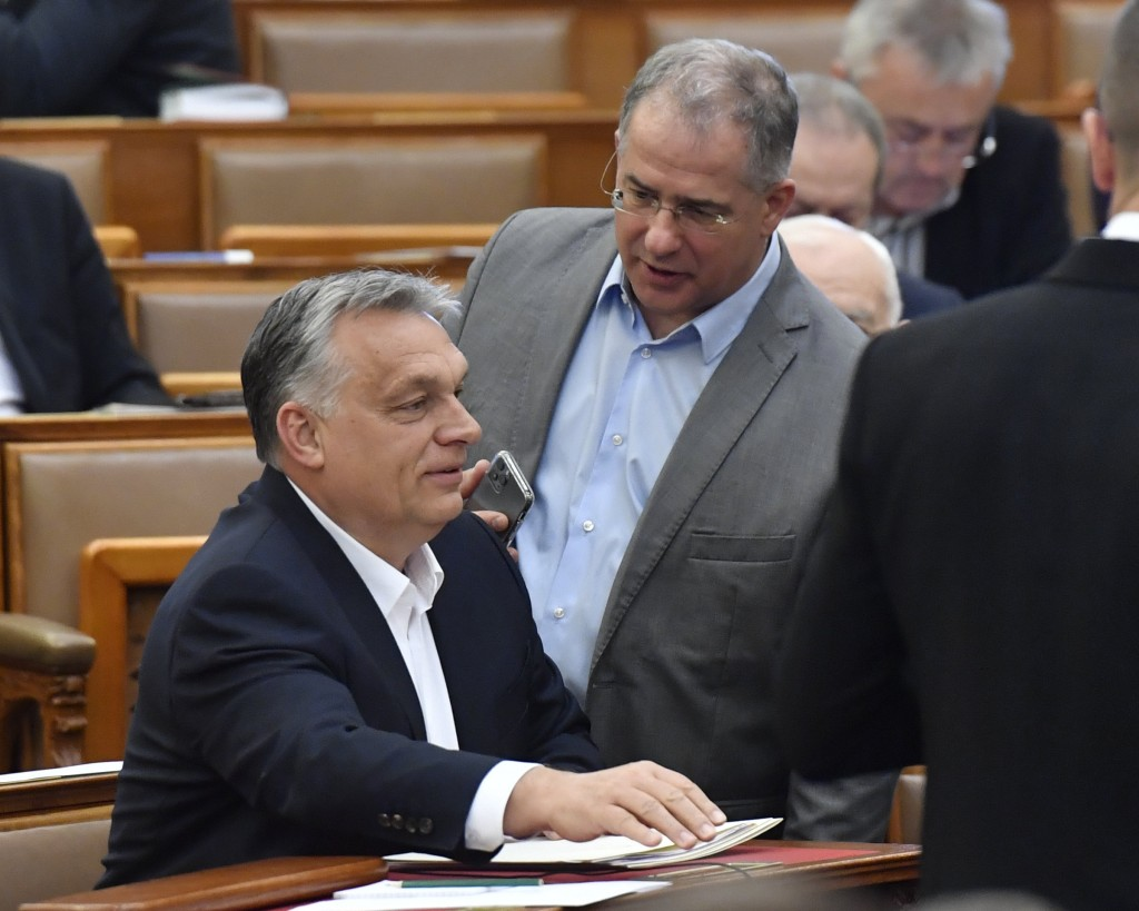 Hungarian Prime Minister Viktor Orban, left, chats with MP of the governing Fidesz party Lajos Kosa during the plenary session of the Parliament in Bu...