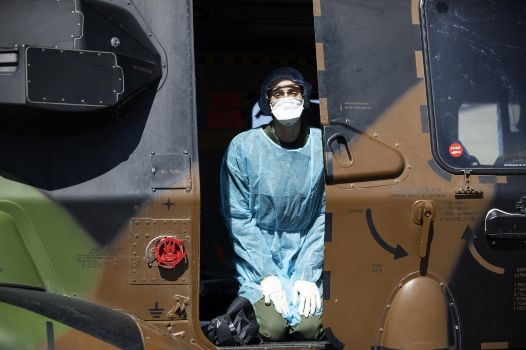 A medical staff kneels in a French military helicopter before evacuating to Switzermand a patient infected with the Covid-19 virus, Monday, March 30 2...