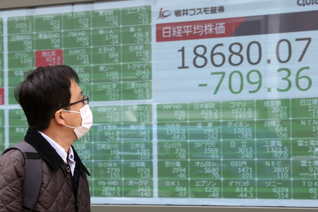 A man looks at an electronic stock board of a securities firm in Tokyo, Monday, March 30, 2020. Asian shares started the week with further losses as c...