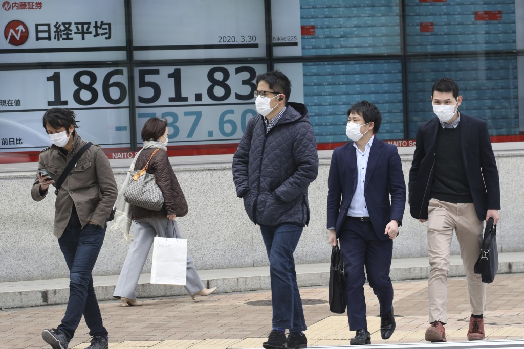 People walk by an electronic stock board of a securities firm in Tokyo, Monday, March 30, 2020. Asian shares started the week with further losses as c...