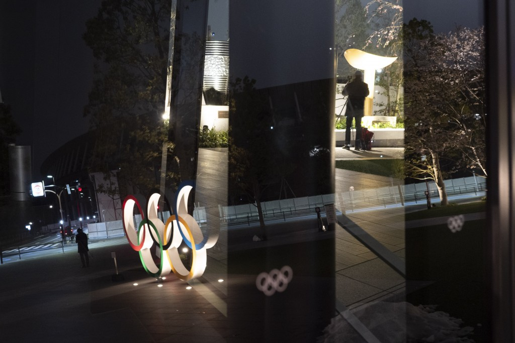 The Olympic rings are reflected on the facade of Japan Olympic Museum Monday, March 30, 2020, in Tokyo. The Tokyo Olympics will open next year in the ...