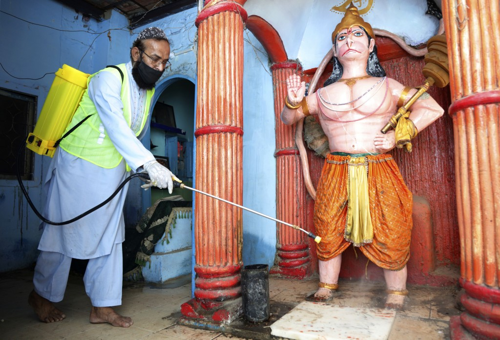 A volunteer disinfects a Hindu temple in an effort to contain the outbreak of the coronavirus, in Karachi, Pakistan, Monday, March 30, 2020. The virus...