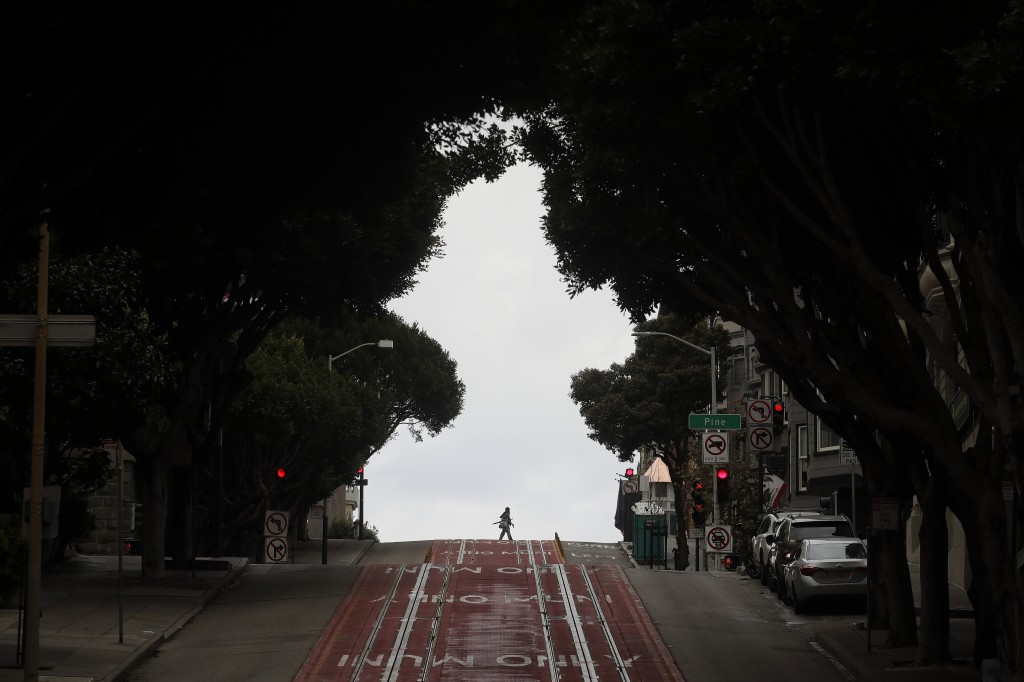 Pedestrians cross Cable Car tracks on Powell Street in San Francisco, Sunday, March 29, 2020. Californians endured a weekend of stepped-up restriction...