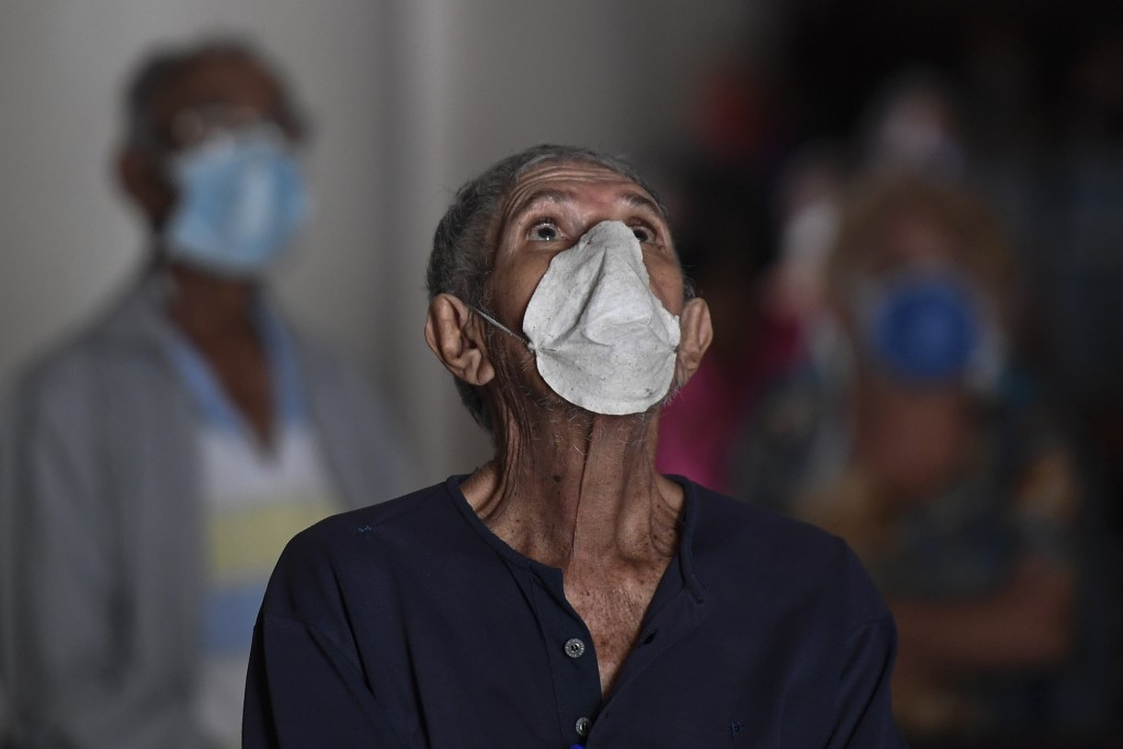 An elderly man, wearing a protective face mask as a precaution against the spread of the new coronavirus, prays during mass at a church in Caracas, Ve...