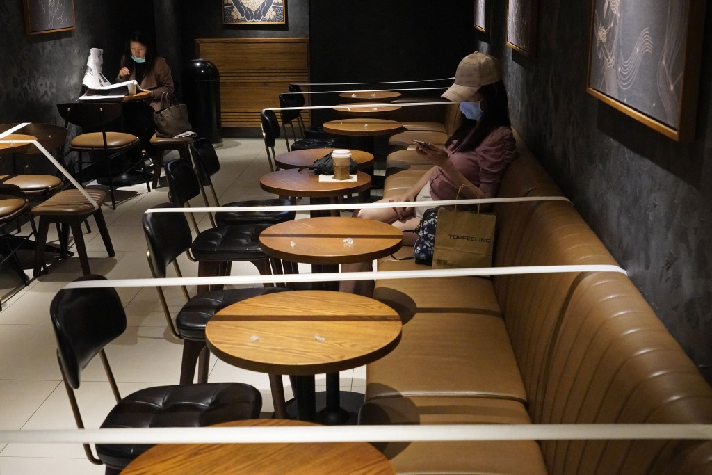Tables and chairs are taped for the social distancing law enforcement to help curb the spread of the coronavirus at a Starbucks coffee shop in Hong Ko...