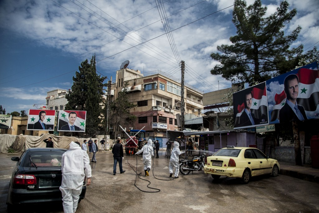 FILE - In this March 24, 2020 file photo, workers spray disinfectant to prevent the spread of the coronavirus, on a street lined with billboards showi...