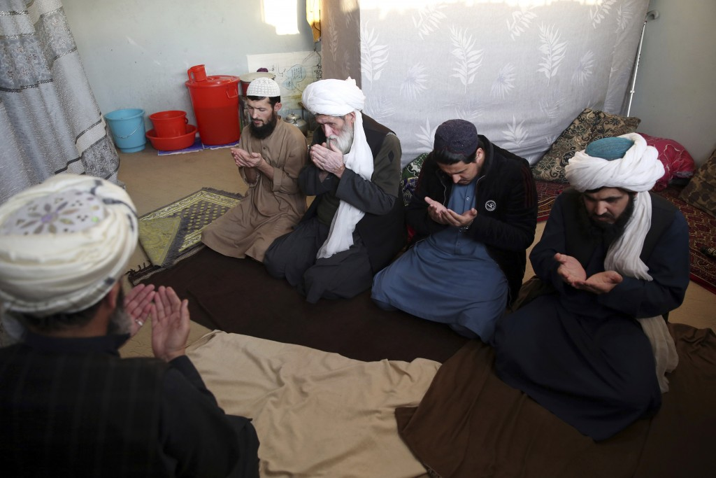 FILE - In this Dec. 14, 2019 file photo, jailed Taliban pray inside the Pul-e-Charkhi Jail, in Kabul, Afghanistan. Afghanistan's largest prison, Pul-e...