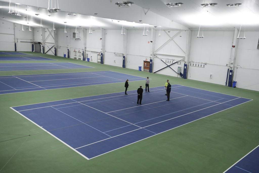 New York City Mayor Bill de Blasio, right, meets with officials on the practice courts at the USTA Indoor Training Center where a 350-bed temporary ho...
