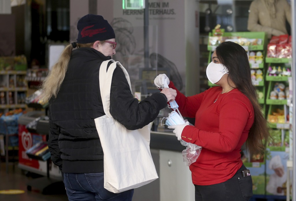 Supermarket employees distribute protective masks to customers in Vienna, Austria, Wednesday, April 1, 2020. In Austria protective masks should be wor...