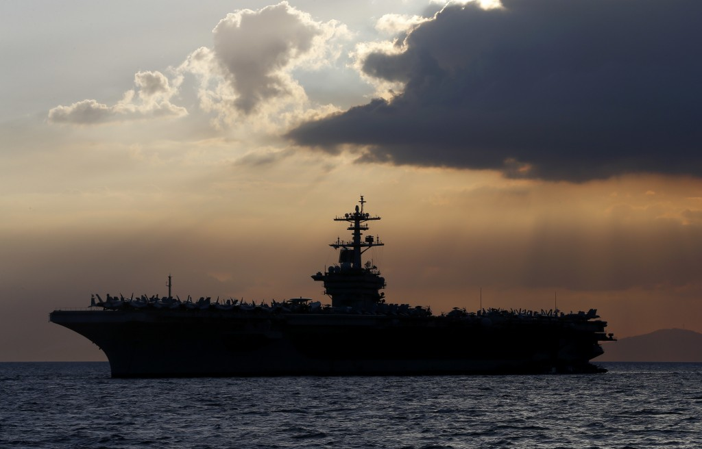 FILE - In this April 13, 2018, file photo the USS Theodore Roosevelt aircraft carrier is anchored off Manila Bay west of Manila, Philippines. The capt...