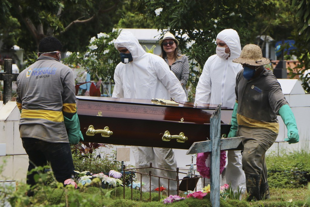 A relative stands at a distance during the burial of Robson de Souza Lopes at Parque Taruma cemetery in Manaus, Brazil, Tuesday, March 31, 2020. Accor...