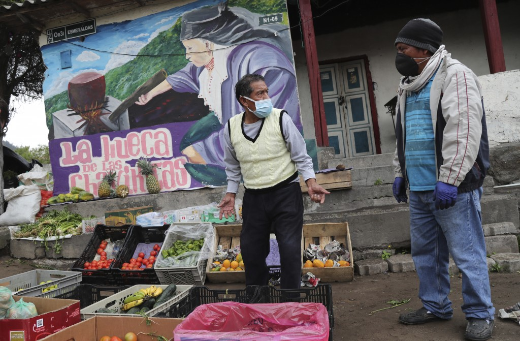 A vendor wearing a mask to protect himself from the spread of the new coronavirus offers fruits and vegetables at an intersection in Quito, Ecuador, T...