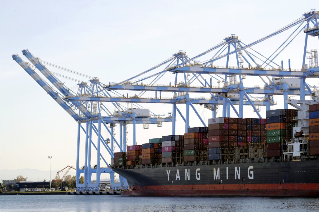 FILE - In this Nov. 4, 2019  file photo cargo cranes are used to take containers off of a Yang Ming Marine Transport Corporation boat at the Port of T...