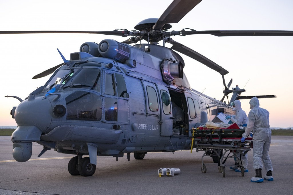 In this photo provided by the French Army Thursday, April 2, 2020, medical staffs evacuate a patient infected with the Covid-19 virus, Wednesday April...