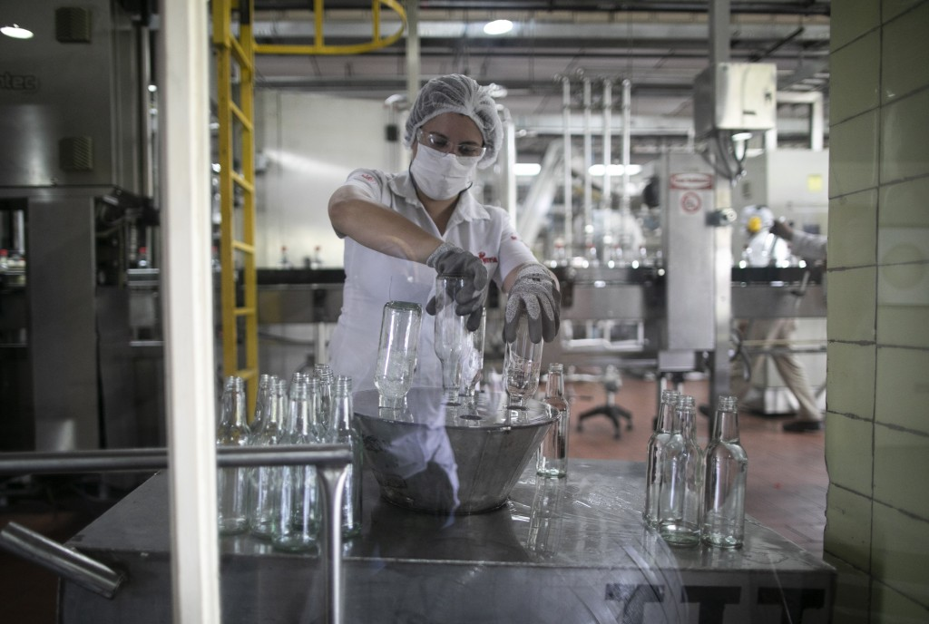 A worker organizes bottles to be filled with antiseptic alcohol at the Santa Teresa rum factory in La Victoria, Aragua state, Venezuela, Wednesday, Ap...