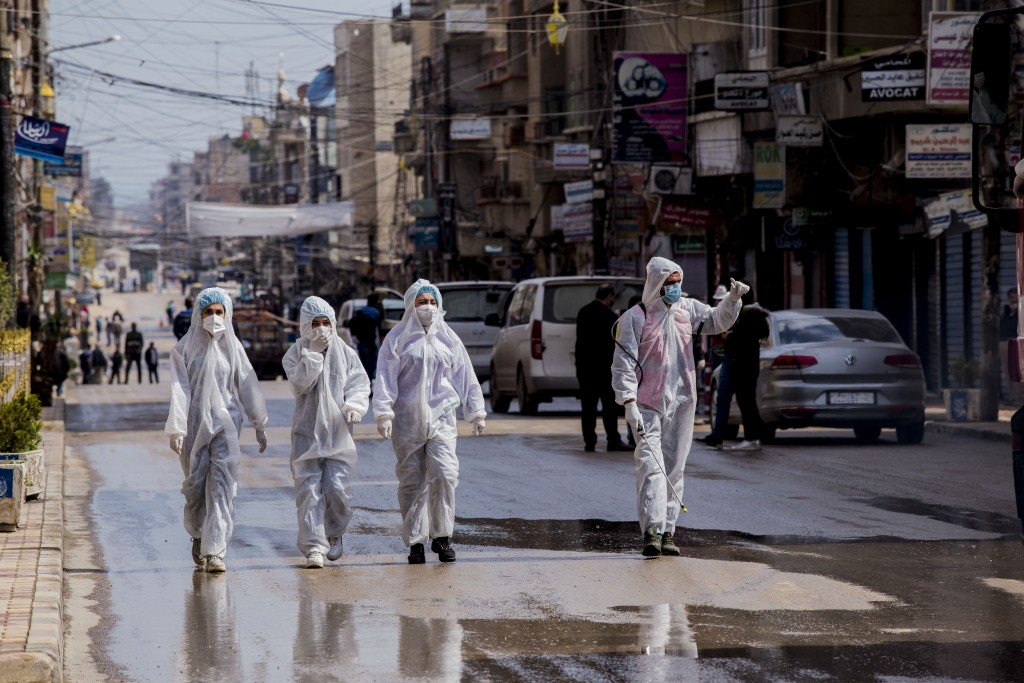 FILE - In this March 24, 2020, file photo, medical workers oversee the disinfection of streets in order to halt the spread of the new coronavirus in Q...