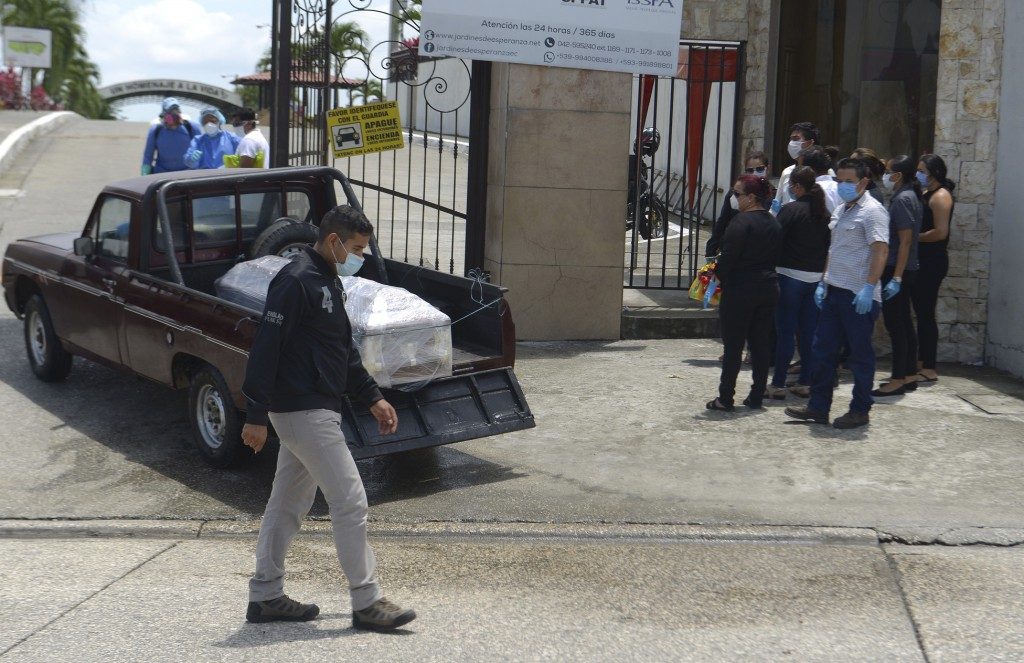 Relatives watch as the remains of a coronavirus victim, which authorities wrap in plastic, arrive to the Jardines de la Esperanza cemetery in Guayaqui...