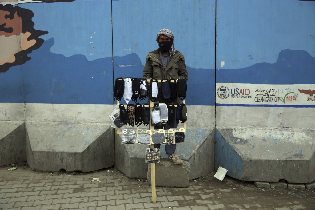 FILE - In this March 23, 2020, file photo, a street vendor selling protective masks aimed at preventing the spread of the new coronavirus waits for cu...