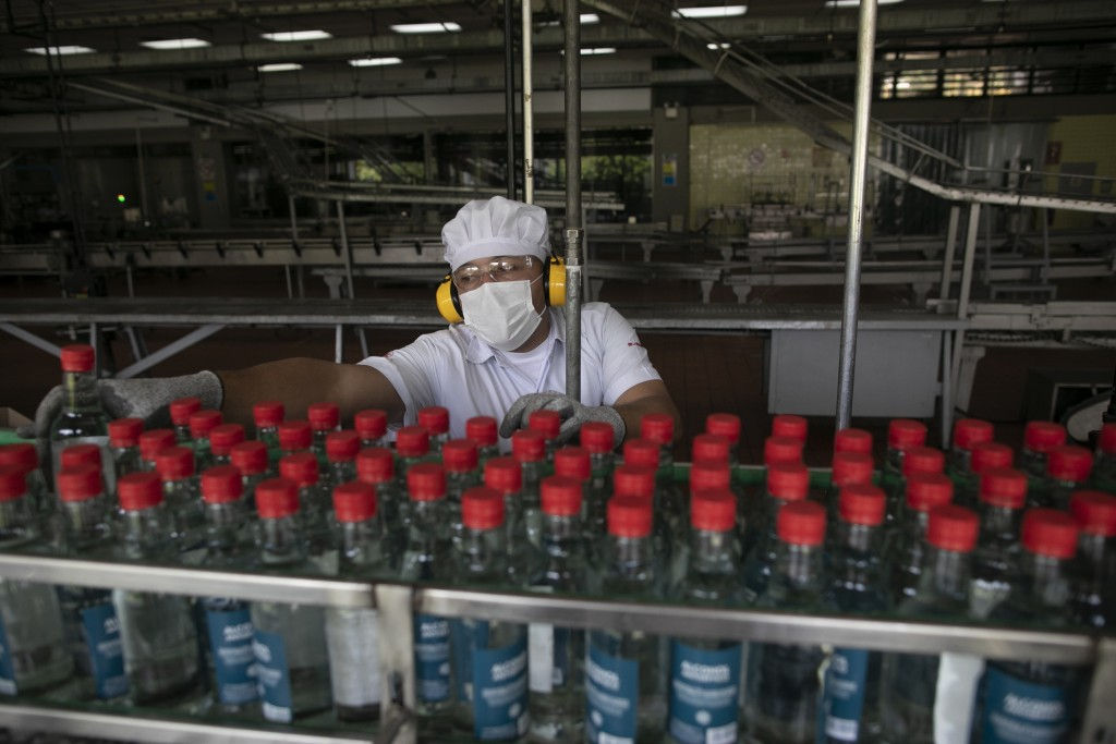 A worker inspects bottles of antiseptic alcohol at the Santa Teresa rum factory in La Victoria, Aragua state, Venezuela, Wednesday, April 1, 2020. Ven...