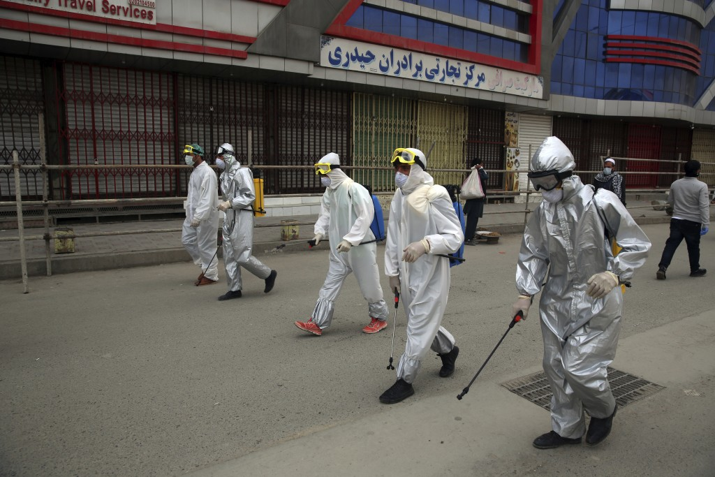 FILE - In this March 29, 2020, file photo volunteers in protective suits spray disinfectant on storefronts to help curb the spread of the coronavirus ...