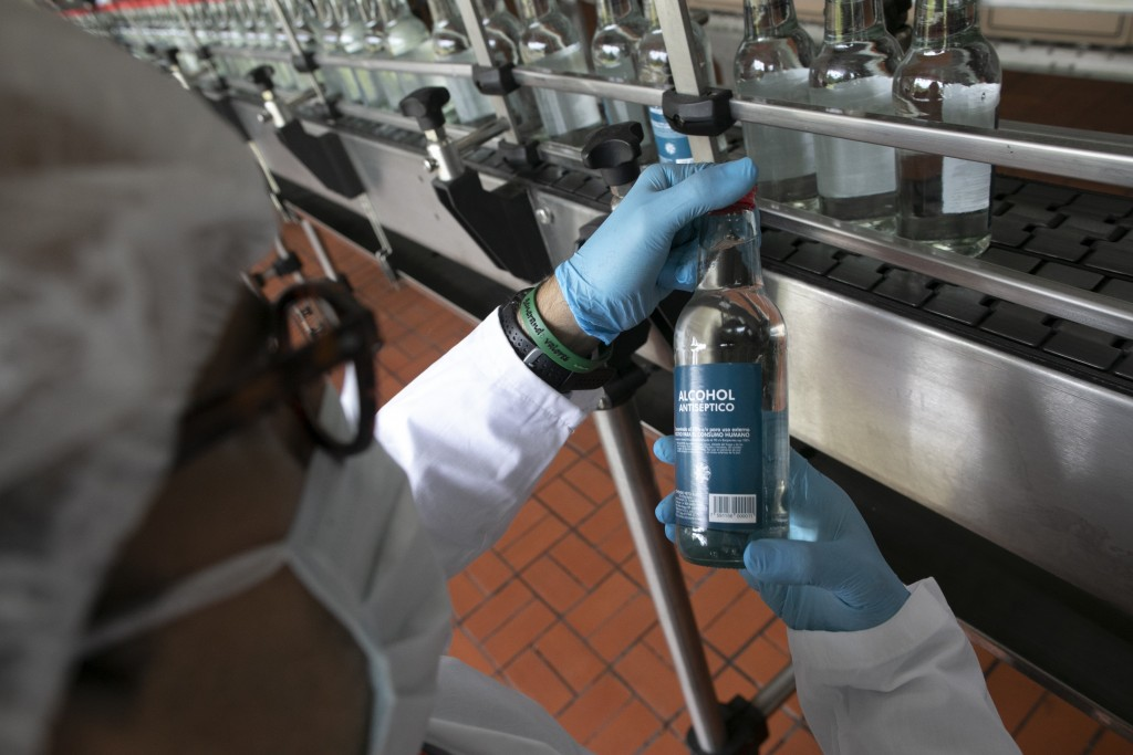 A worker inspects a bottle of antiseptic alcohol at the Santa Teresa rum factory in La Victoria, Aragua state, Venezuela, Wednesday, April 1, 2020. Ve...