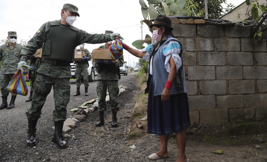 Soldiers deliver food to a woman who cannot leave her house because of the government's request that people don't leave their homes to prevent the cor...