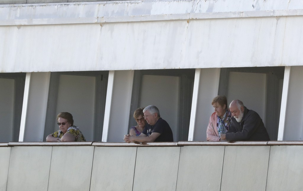 Passengers look out their balconies aboard the cruise ship Rotterdam as they wait to disembark at Port Everglades, Thursday, April 2, 2020, in Fort La...