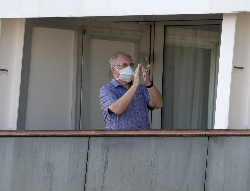 A passenger claps from his balcony after a crew announcement aboard the cruise ship Rotterdam as passengers wait to disembark at Port Everglades, Thur...
