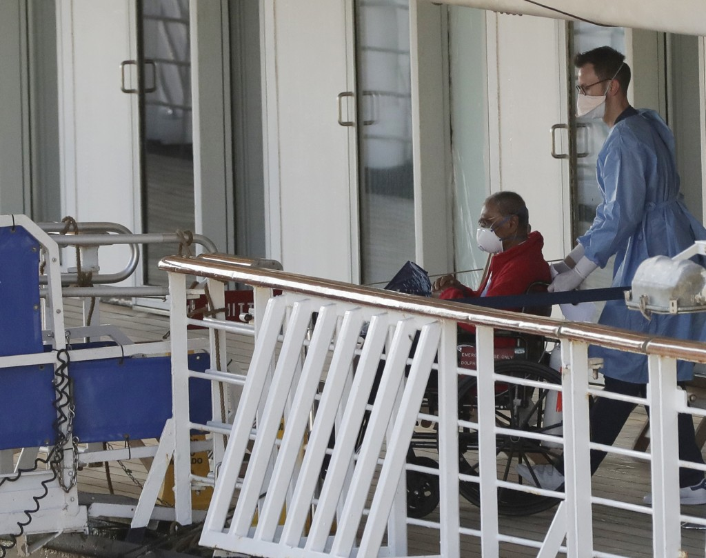 A person in a wheelchair is taken off the cruise ship Rotterdam after docking at Port Everglades during the new coronavirus pandemic, Thursday, April ...