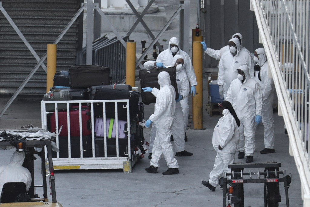 Workers in protective gear unload luggage from Carnival's Holland America cruise ship Zaandam as it is docked at Port Everglades during the new corona...